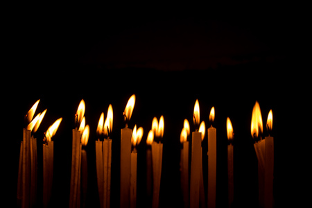 Many christmas candles burning at night on the black background. Candle flame set isolated in black background. Group of burning candles in dark with shallow depth of field. Close-up. Free space.