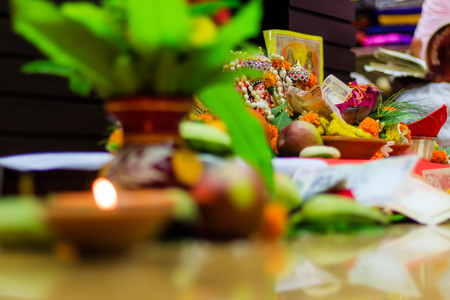 Selective focus. Diwali puja or Laxmi puja set up at home. Oil lamp or diya with crackers, sweet, dry fruits, indian currency, flowers and statue of Goddess Laxmi on a festival Diwali night. Stock Photo