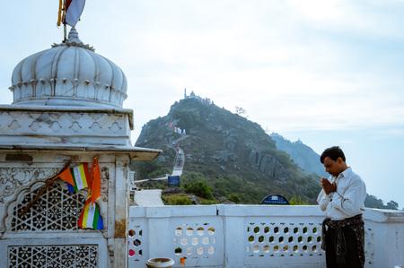 MUKTAGIRI, MADHYA PRADESH, INDIA MAY 5 2016: A jain pilgrim devotee meditating in front of famous historical Jainism Temple. Muktagiri is a Jain Pilgrimage center and UNESCO World Herutage site. Editorial