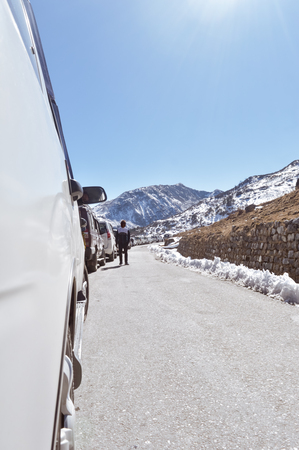 Traffic jam and Highway blockage due to snowfall at Tsomgo Lake. Tourist vehicles lined up to climb in step hill region of himalayan mountain valley.
