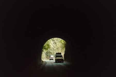 Car drives through the Highway Urban Tunnel. View from badly lit tunnel from a fast moving car on a sunny day. Motion Blur Background.