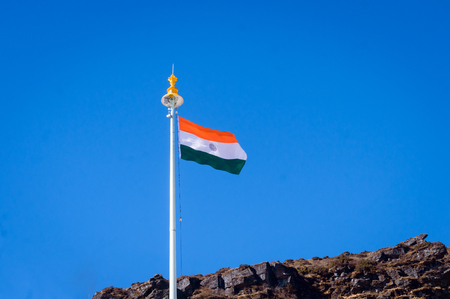 Indian tricolor national flag on a flagpole, waving in wind on mountain top. Blue sky background. Isilated Close up. 26 January Republic day, 15 August Indian Independence day, Travel tourism concept