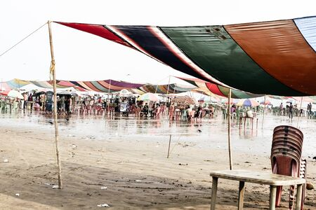 Versova beach, Mumbai India 10, Jan 2019: Beach market View of crowded with tourists and vendors in during new year festival, causes water pollution due to plastic and pile of garbage. Editorial