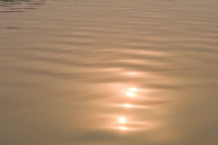 Beautiful sunset water background. Soft wave of the sea. At twilight times and reflections. Golden and orange colors in the waves. An attractive design of reflections of sun at sunset. Banco de Imagens