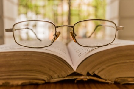 An open book and a specs or eyeglass on wooden table, on a warm sunny morning, side view close up. Education or Holiday Concept. Isolated background in selective focus, shallow depth of field