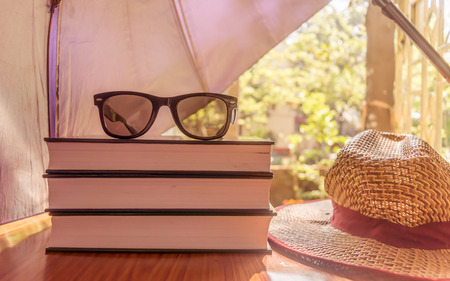 Sunburn risk concept protect your skin from temperatures, Umbrella protecting beautiful woman things. Books sunglasses and a straw hat. Summer holiday concept with copy space room for text. Stock Photo