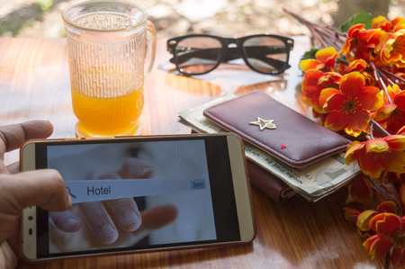 A business traveler search for reservation of holiday home. Close-up Of screen interface of booking hotels using cell phone along with travel accessories. Summer time background with natural sun light