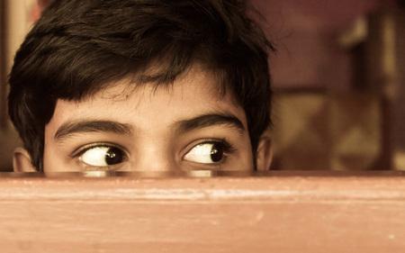 Junge, der neugierig durch ein Fenster nach draußen schaut.