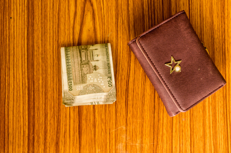 Indian five hundred (500) rupee cash note in brown color wallet leather purse on a wooden table. Business finance economy concept. High angel view with copy space room for text on bottom side of image Stockfoto