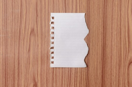 Sheet of notebook paper with torn edge blank ripped piece on isolated over wooden table background. Empty Damaged Rip Paper Shape. Clipping path, copy space room for text, educational design concept Фото со стока
