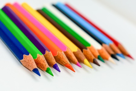Close-up of a selection of Multi Colored pencils crayons, stick together arranged in a row line bar graph on white background, flat lay. Selective focus, blur image. Back to school creativity concept.