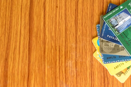 Stack of different bank credit card placed at the edge of wooden table. Business finance economy concept. High angel view with copy space room for text on left side of image. Banco de Imagens