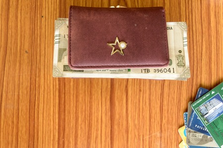Five hundred (500) cash note in brown ladies purse and stack of credit cards on a wooden table. Business finance economy concept. High angel view with copy space room for text on front of image.