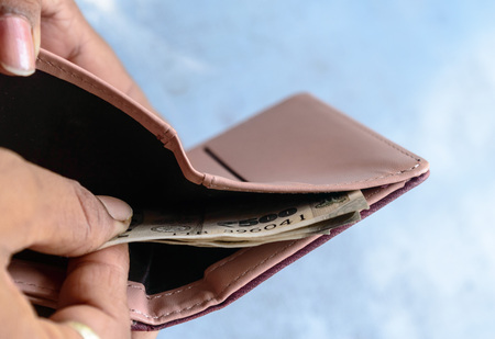 Businessman putting or taking out or paying Indian rupee banknotes from leather wallet. Isolated white background. Earning crisis growth bribe corruption bankrupt concept. Selective focus Close-up