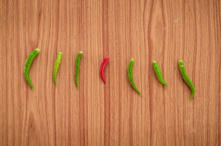 A Red hot spicy thai chili peppers or Mirchi among green chilli arranged in a horizontal row on wooden background, flat lay. Top view. Standing Out From The Crowd Concept with copy space room for text