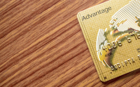 A part of credit card lying on wood table background. Online shopping concept. Imagens