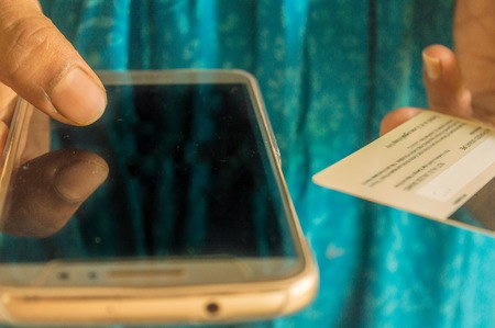 Out of focus Asian and Indian woman paying bill at home with online payment technology via internet, with plastic credit card and smart phone with white blank empty screen. Online shopping concept.