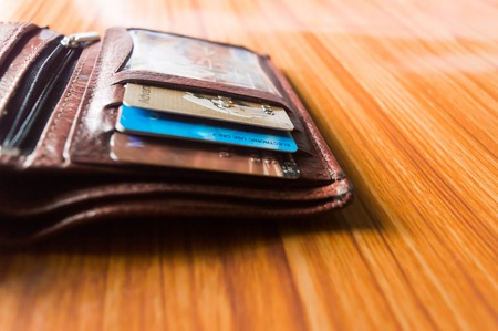 Selective focus. Men's Leather Brown open wallet isolated on wooden background. Room for for add your text or object. Imagens