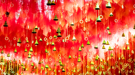 Golden bells with greeting lucky word on red ribbon at Kalighat Kali Mandir Temple Kolkata. Pilgrims people wish and hang it on rope for pray. Merry christmas happy new year concept background texture Imagens