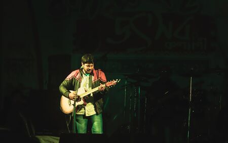 Kolkata India 1 May 2019: Guitarist performing on. Rock Concert venue with lit bright colorful stage lights and silhouette of fans or cheering crowd in front of it. Summer music background concept Redactioneel