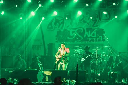 Kolkata India 1 May 2019 - Guitarist performing rock concert venue with lit bright colorful stage lights and fans or cheering crowd in front of it. Summer music festive background concept.