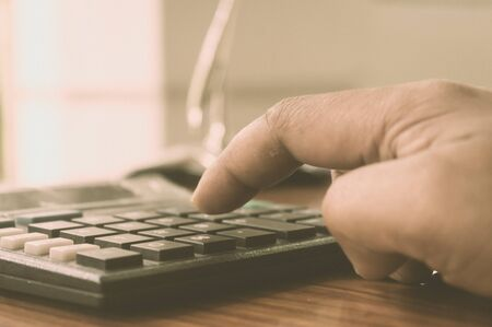 Close up of Press the right button. Calculator with finger. Fingers pressing the buttons of calculator. A businessman typing hand calculating numbers. Counting on vintage background isolated.