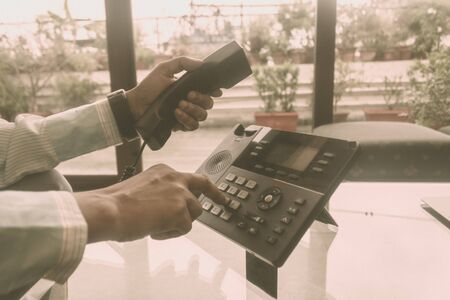 Close up male of hand holding telephone receiver and dialing a telephone number to make a call using Landline phone for Business Talk. Global communication, business support, customer care concept.