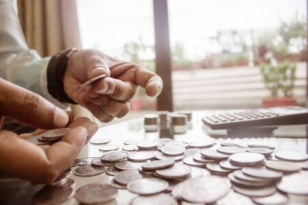 Cropped Image Of Businessman counting coins Using Calculator at Desk In Office. Businessperson Hand Counting Coins. Business Finance Savings and Investment concept. Conceptual Save money for future. Imagens