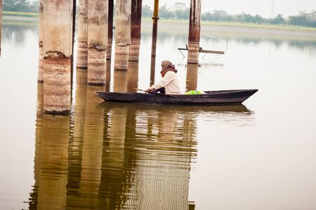 Kerala, India, January 10, 2018 – A local Active senior Man rowing his boat away from shore at a Kerala backwater area on sunset Dusk.