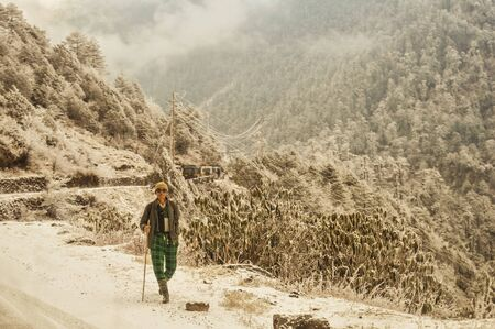 A Mature old (a man of Nepalese ethnicity) solitary hiker on a hiking trail walking alone in a beautiful winter environment of North east Himalayan Mountain range. Nepal, South Asia.