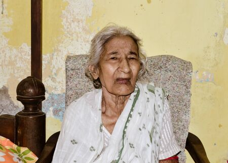 Portrait of smiling Active senior Asian and Indian Ethnicity woman of 82 years sitting on chair resting at home while looking at camera.