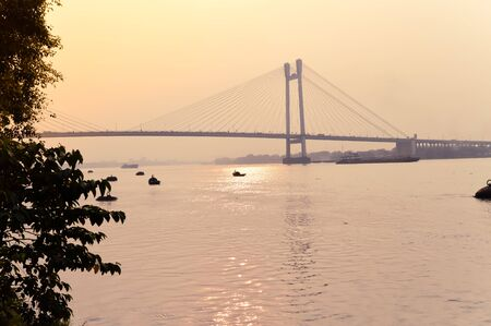 Sunset over Vidyasagar Setu (a modern Cantilever Spar Cable-Stayed Bridge) in a summer evening on the river Hooghly. Silhouette view from distant. Howrah city, Kolkata, West Bengal, India, South Asia. Stock fotó