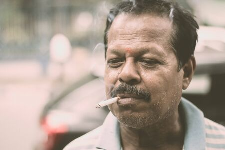 Portrait of a A mid adult senior mature man of Asian and Indian Ethnicity is smoking cigarette. Front View. Close up. Photography taken on 31 May 2019 on World No Tobacco or anti Tobacco Day, in a city street of India, South Asia. Reklamní fotografie
