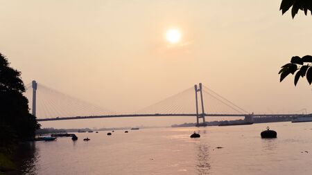 Sunset over Vidyasagar Setu (a modern Cantilever Spar Cable-Stayed Bridge) in a summer evening on the river Hooghly. Silhouette view from distant. Howrah city, Kolkata, West Bengal, India, South Asia.