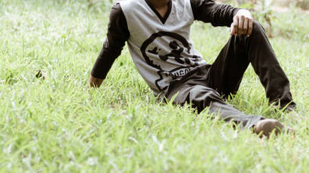Close up Cropped image of young man in casual clothing sitting over green grass in the park at morning time of day.