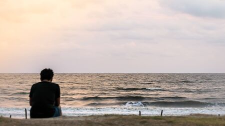 Blur image of a solitary man sitting alone at the beach in sunset time. Rear View of a lonely thinking person in wilderness area. Rest, relax, leisure activity background concept.