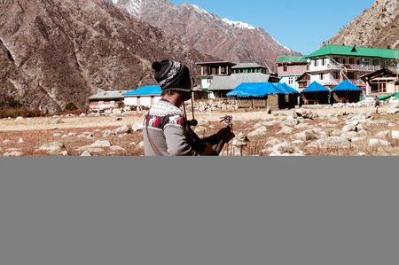 A solo traveler hobbyist musician playing guitar alone in the silence of Himalayan mountain valley and sound of guitar strings. Summer music Inspiring environment in outdoors. Sangla India South Asia.