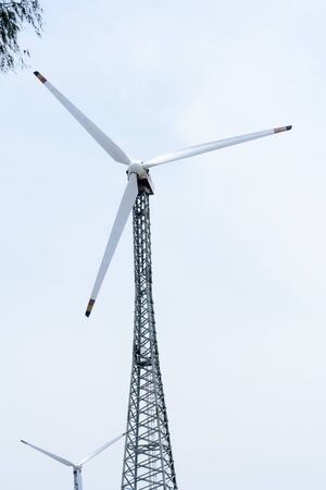 Taller hybrid tower lattice wind turbine build of rolled steel (tubular segmented) install high up 200 feet over land with 100m diameter rotor. Wind turbines widely used in renewable energy resource. In industry like roads, power collection network, substation, meteorology. Stock Photo