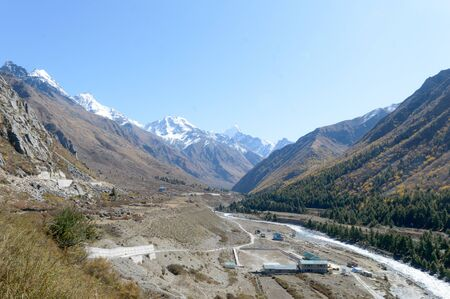 Panoramic Himalayas Highland Islands Mountain valley, panorama of city Sangla Valley, Chitkul village, from the hiking trail in Himalayas Mountains, in summer season. Himachal Pradesh India