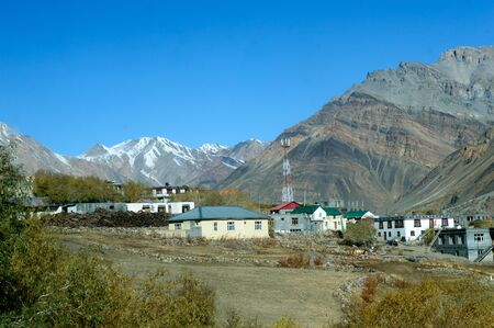 Village at Foothill of Himalayas. Small Villages In The Foothills Of Himalayan picturesque valley. A beautiful indian landscape of a town city at foothills of snow capped Mountain ranges. Kaza India Stok Fotoğraf - 138608015