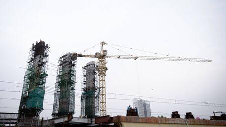 A tall high crane Equipment work in progress in a construction site of a housing development.
