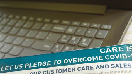 Part of Newspaper showing pledge to overcome Corina virus epidemic COVID - 19. Laptop keyboard out of focus Background.