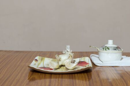 Garlic Salt on wooden table. Garlic salt is a seasoned salt made of a mixture of dried, ground garlic and table salt with an anti-caking agent ( calcium silicate)
