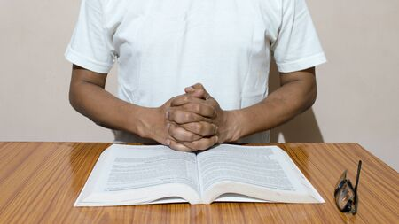 A man holding his hands on open holy book. Prayer concept. Stock Photo