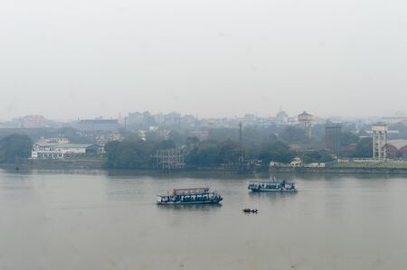 Panoramic Kolkata riverside city life in a winner foggy evening. Ariel view Kolkata in Hooghly riverbank West Bengal India South Asia Pacific. Photography from rooftop. Stock Photo