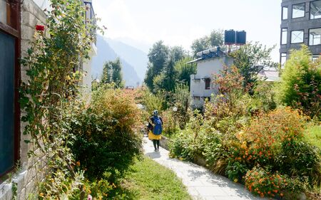 Rear View solo woman in hiking sportswear and with a backpack on her shoulders. Sporty woman with backpack walking outdoors. Travel girl stands on garden front yard walking away. Adventure Sports Healthy lifestyle background.