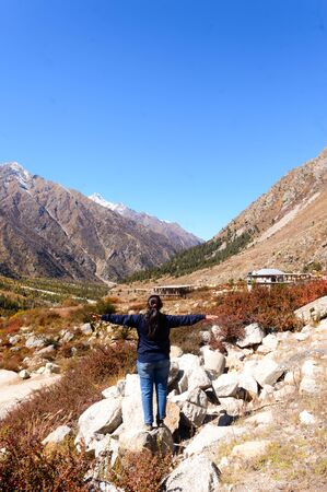 Rear View of Solo Woman Indian traveler in winter casual standing alone with arms outstretched in remote mountain valley. Snow capped Himalayan mountain forest blue sky in background. Spiti Valley Himachal Pradesh India South Asia Pac