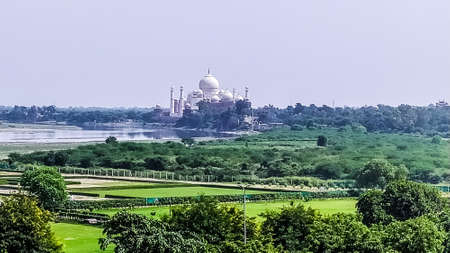 The Taj Mahal from a distance. A different view from far distant of Taj Mahal in the distance with lush greeneries in front. Photography from Agra Fort, South Asia Pac India.