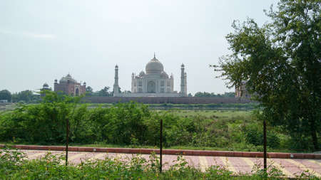 The Taj Mahal seven wonders of the world. A different view of Taj Maha from far distant with lush greeneries in front. Photography from Agra Fort, South Asia Pac India. August 15 2019