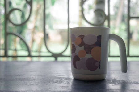 Coffee cup and window. Morning cup of coffee. Coffee cup isolated from in window sunlight in background.